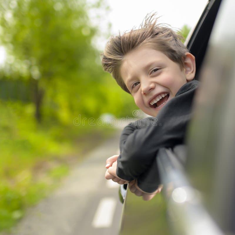 Drömma pojken som ut ser från bilfönstret arkivfoton