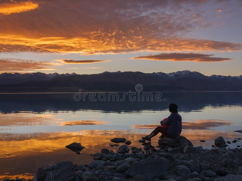 Drömmare kontur av kvinnasammanträde längs sjön på solnedgången, mänsklig styrka, psykologibegrepp fotografering för bildbyråer