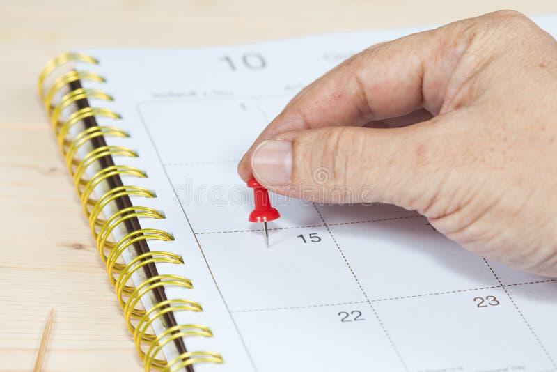 Drücken Sie ein Stiftkennzeichen auf Kalender von Hand ein stockfotos
