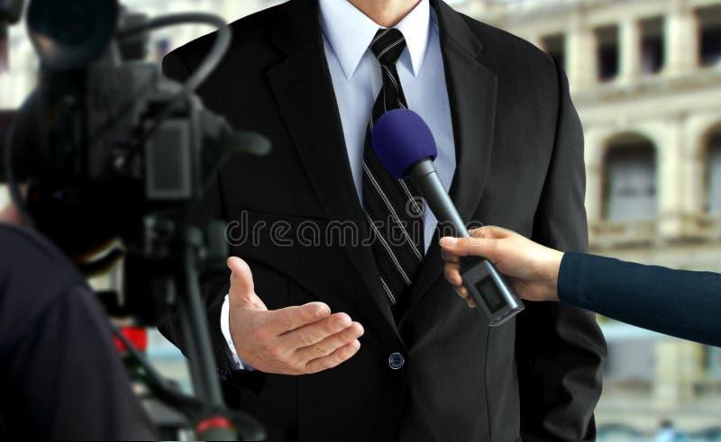 Drücken Sie Interview mit einem Mann im schwarzen Anzug lizenzfreies stockbild