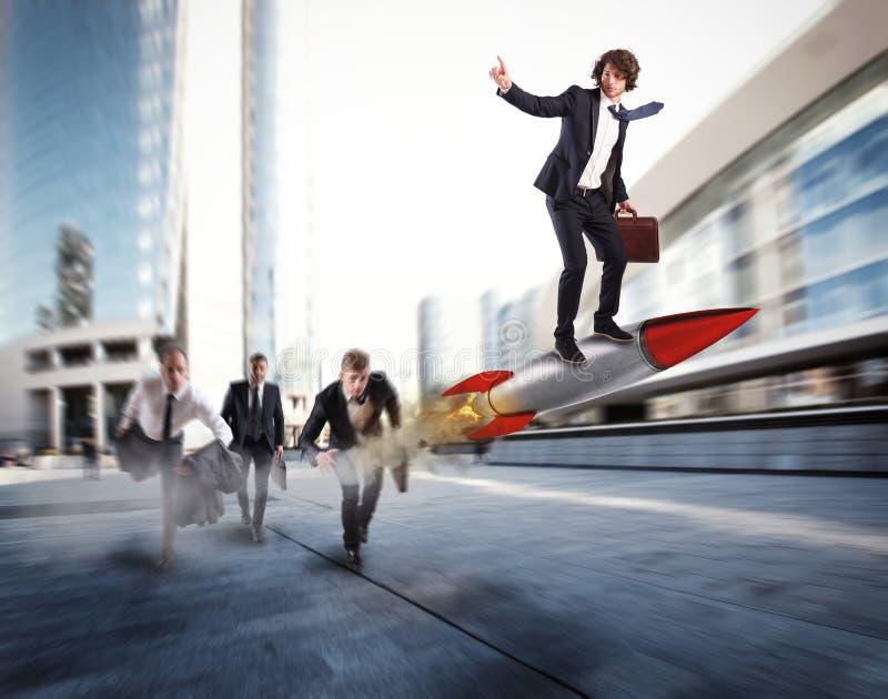 Drücken Sie, um die Ziele vor den anderen zu erreichen Geschäftsmann gewinnt eine Herausforderung, die eine Rakete reitet stockbild
