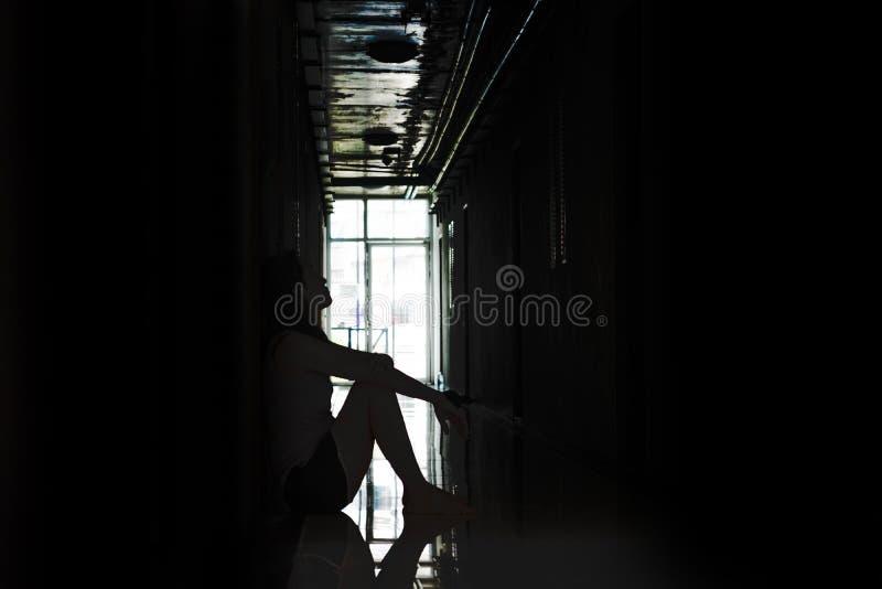 Drücken Sie und die hoffnungslose Frau nieder, die in der Dunkelheit sitzt stockfotografie