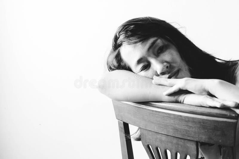 Drücken Sie und die hoffnungslose Frau nieder, die auf Stuhl sitzt lizenzfreies stockbild