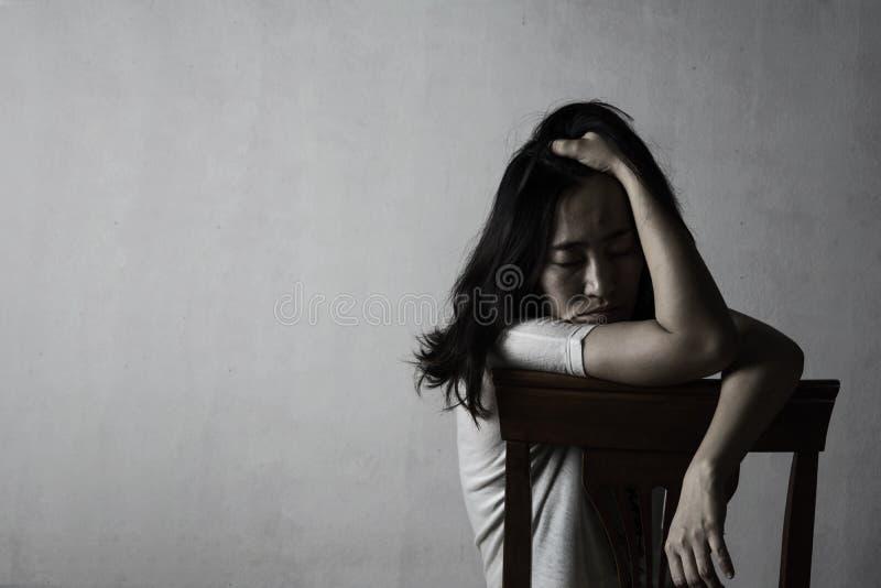Drücken Sie und die hoffnungslose Frau nieder, die auf Stuhl sitzt stockfoto