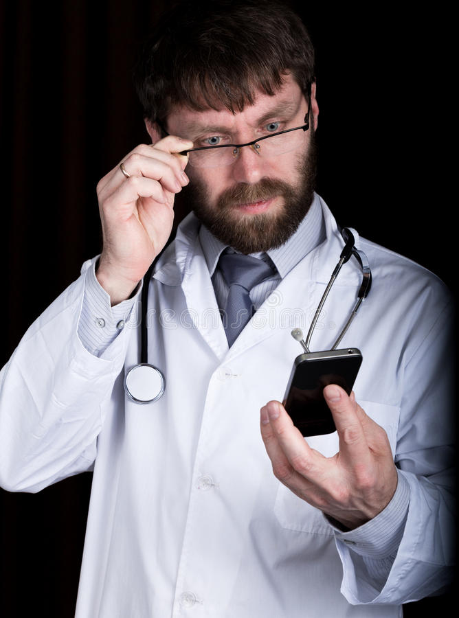 Dr. bearded man in a white medical robe, stethoscope on his neck, emotionally talking on phone stock image