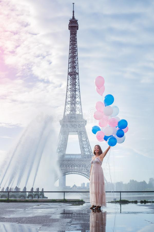 Dr?m- lopp - ung kvinna med ballonger som g?r n?ra Eiffeltorn i Paris royaltyfri fotografi