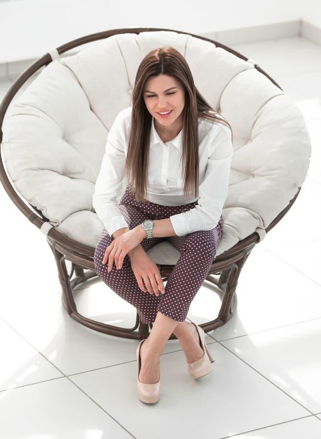 Dr?mma sammantr?de f?r ung kvinna i en mjuk rund stol royaltyfri fotografi