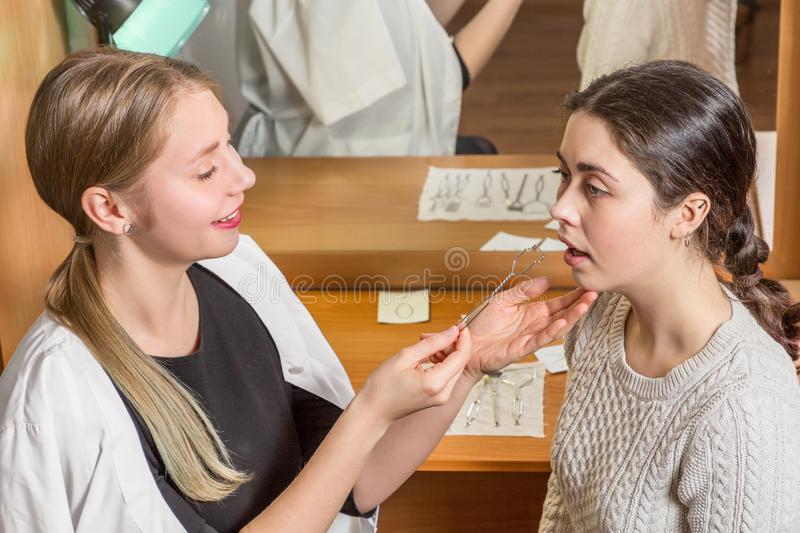 Dr. speech therapist uses a probe to correctly position the patient`s tongue for pronunciation royalty free stock photo