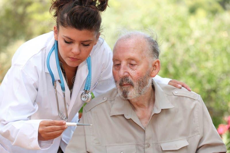 Dr. termômetro da leitura do homem superior imagens de stock royalty free