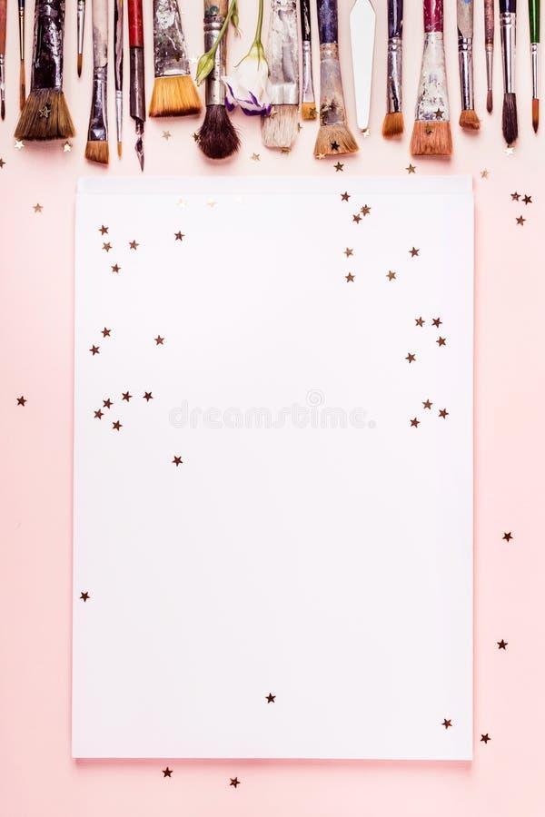 Dra albumramen, radborsten och guld- stjärnor på rosa bakgrund arkivfoto