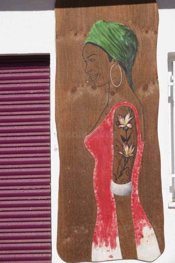 Dra av en le kvinnakontur, med en röd halsduk för klänninggräsplanhuvud och stora örhängen royaltyfria bilder