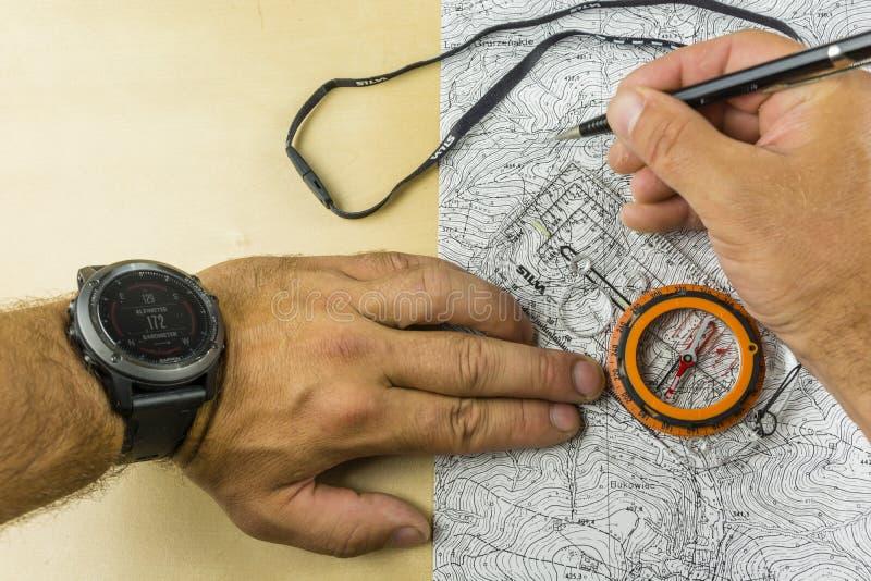 Dra en rutt och riktningen av att gå i fältet som baseras på en topographic översikt och en kompass royaltyfri bild