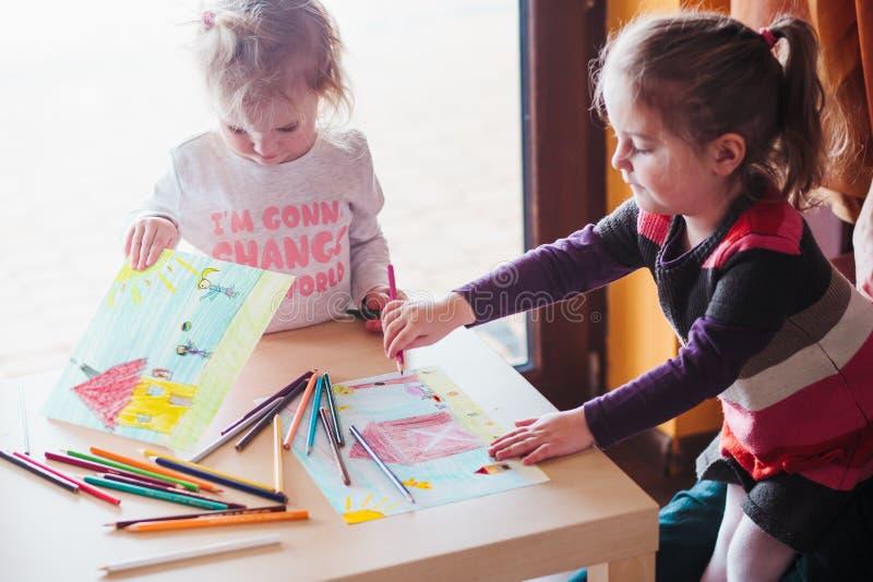 Dra för två små flickor färgrika bilder genom att använda blyertspennafärgpennan royaltyfri foto