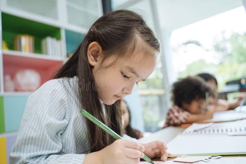Dra papper för små förskole- ungar med färgblyertspennor stående av flickan med vänutbildningsbegrepp royaltyfria bilder