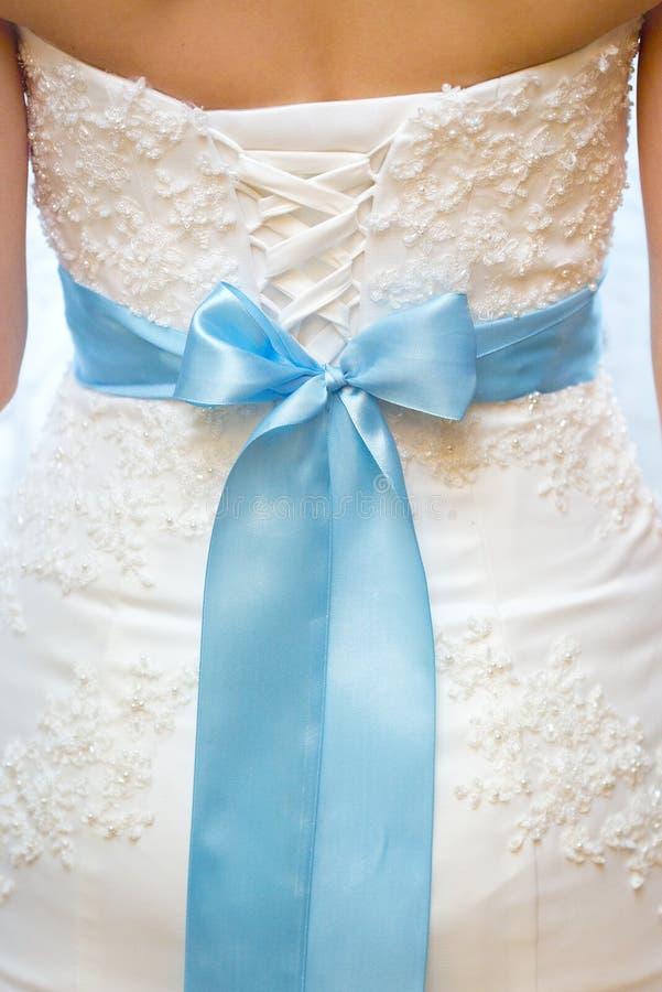 Dra tillbaka av brud i vit snör åt bröllopsklänningen med strumpebandsorden royaltyfri foto