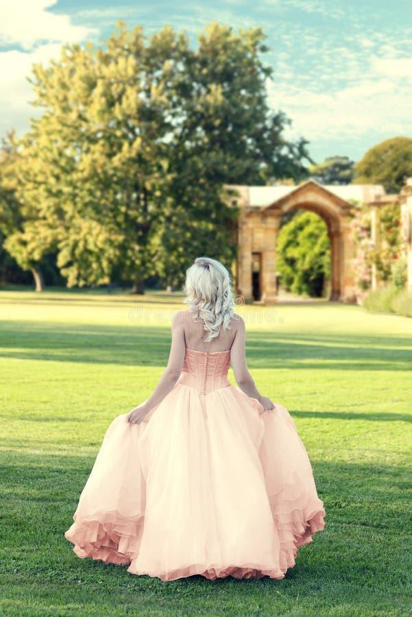 Dra tillbaka av den bärande aftonklänningen för kvinnan som går i formell trädgård royaltyfri bild