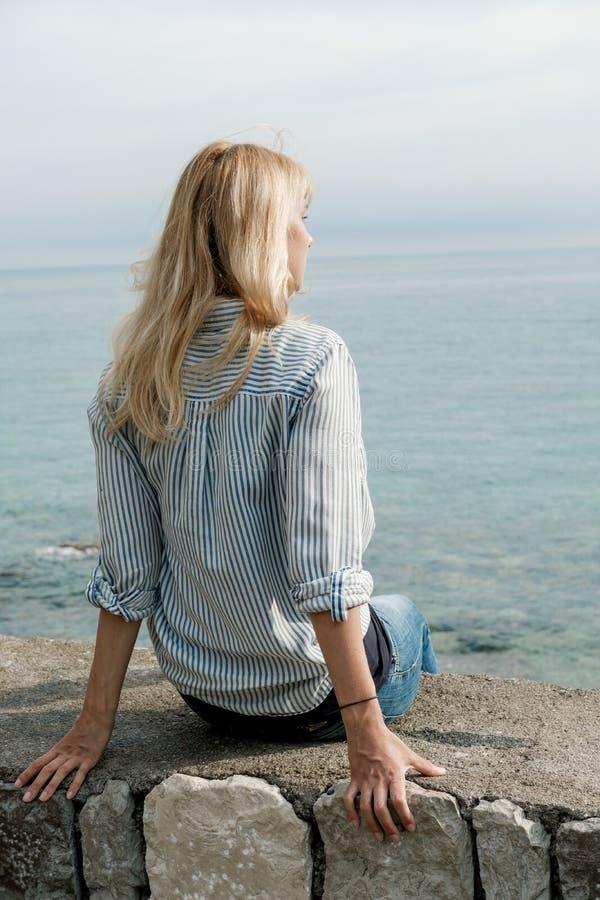 Dra tillbaka av den blonda kvinnahandelsresanden som tycker om sikterna på havet i summe royaltyfri fotografi