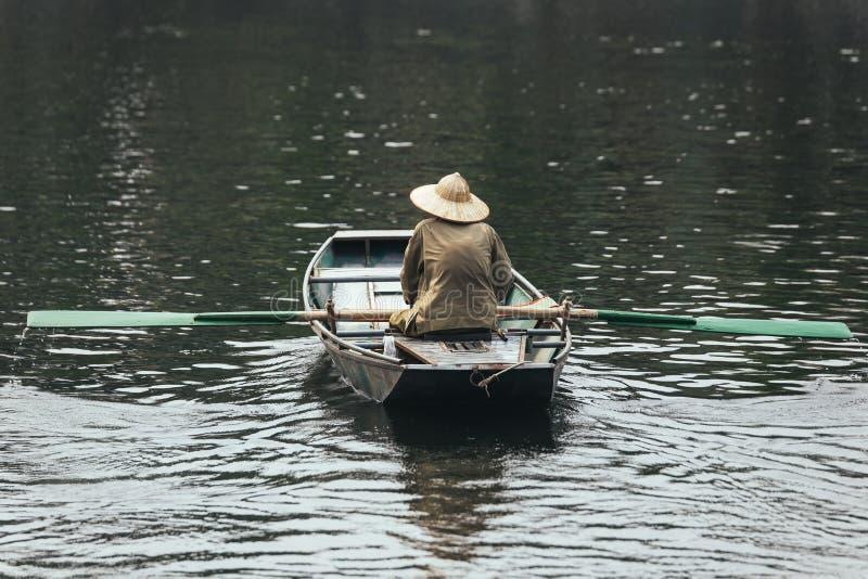 Dra tillbaka av ekamannen som bär den gröna skjortan och koniskt hattsammanträde i ett fartyg med skovlar över floden i bakgrund royaltyfri bild