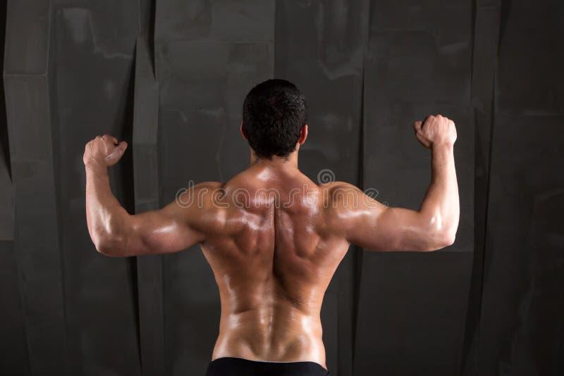Dra tillbaka av en muskulös man på en mörk bakgrund royaltyfria bilder