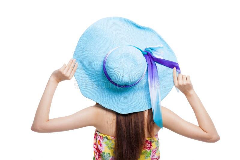 Dra tillbaka av flickan som rymmer en hatt över vit royaltyfri bild
