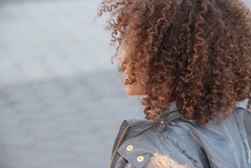 Dra tillbaka av flickans lockiga huvud av hår fotografering för bildbyråer