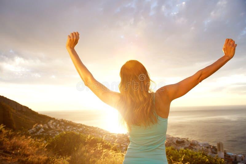 Dra tillbaka av kvinna med armar som är utsträckta under solnedgång arkivfoton