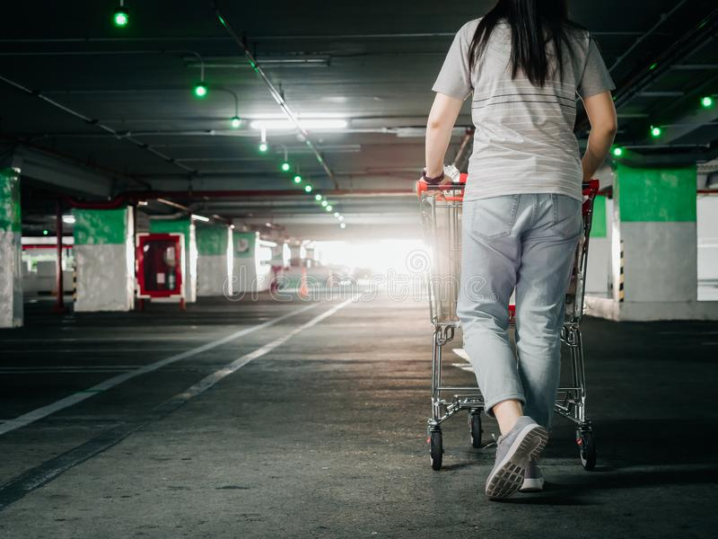Dra tillbaka av kvinna med flyttning för shoppingvagn och sök efter hennes bil i ca royaltyfri foto