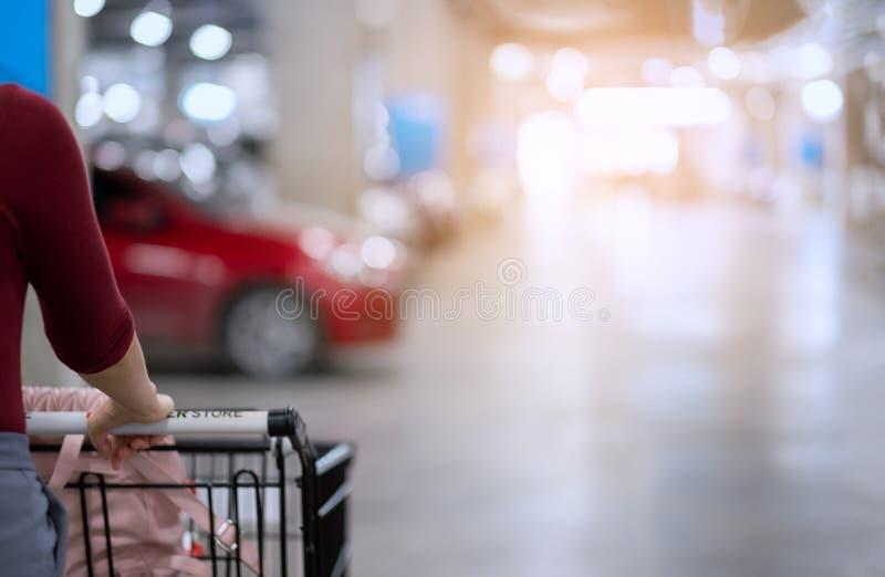 Dra tillbaka av kvinna med flyttning för shoppingvagn och sök efter hennes bil i ca arkivbild