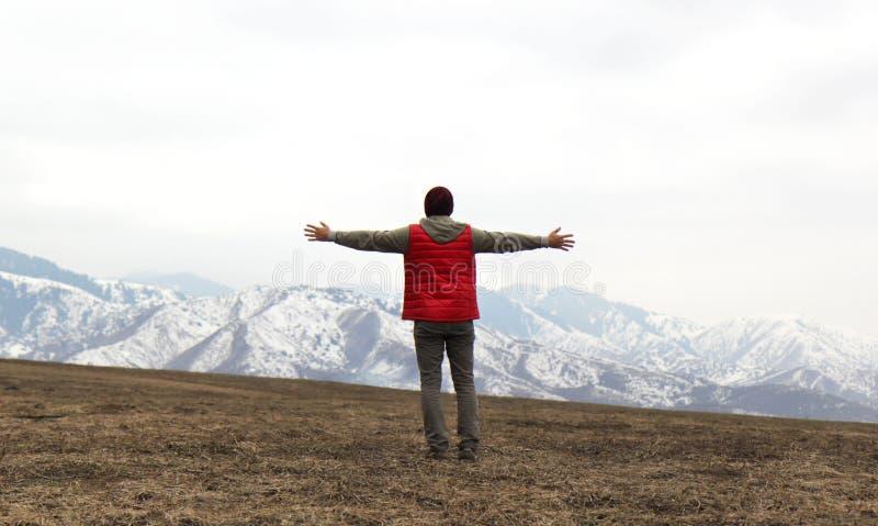 Dra tillbaka av man i röd waistcoat med händer till sidan på bergbakgrunden royaltyfria foton