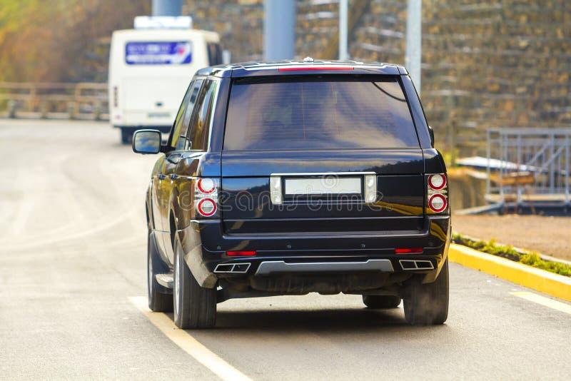 Dra tillbaka av ny svart SUV bilparkering på asfaltvägen arkivfoto