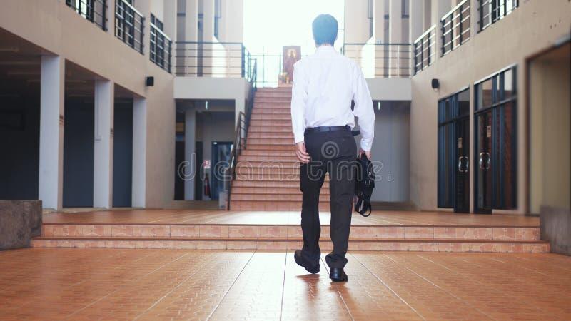 Dra tillbaka av sikt av den unga affärsmannen i en dräkt går med en portfölj i ett affärscentrum arkivbild