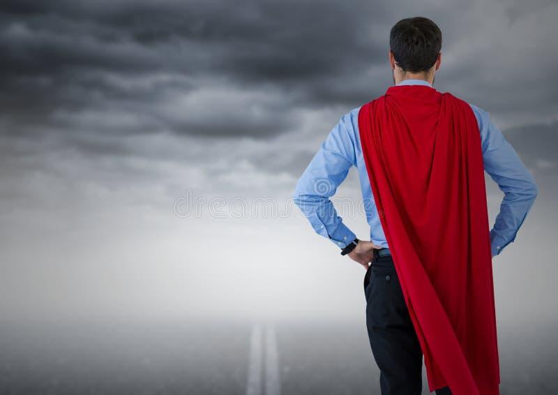 Dra tillbaka av superhero för affärsman med händer på höfter mot vägen och stormig himmel stock illustrationer