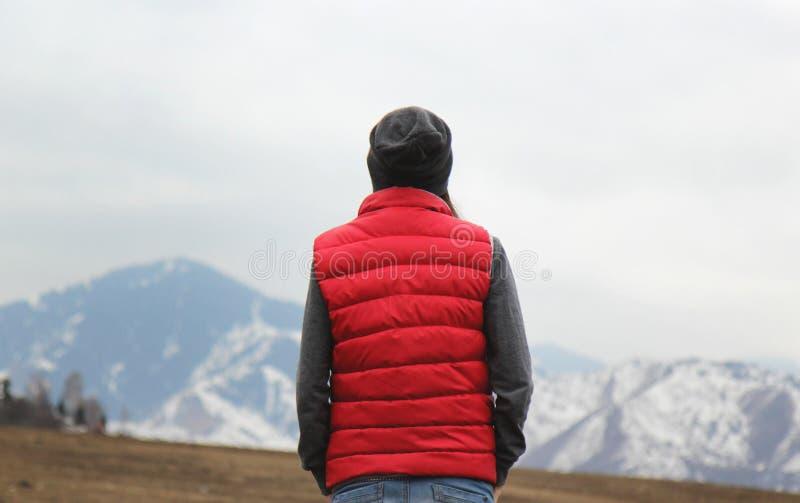 Dra tillbaka av ung kvinna i röd waistcoat och hatt på bergbakgrunden arkivfoton
