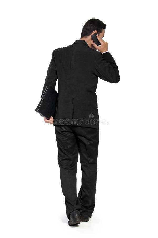 Dra tillbaka skottet av att gå affärsmannen, samtal på telefonen royaltyfri fotografi