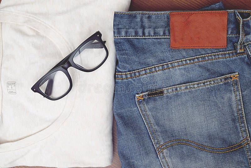 Dra tillbaka till grundläggande blå jean och en skjorta för vit t arkivfoto