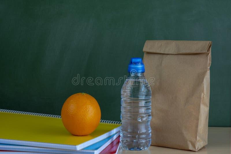 Dra tillbaka till sammanträde för säcken för skolalunch på läraren Desk royaltyfri foto