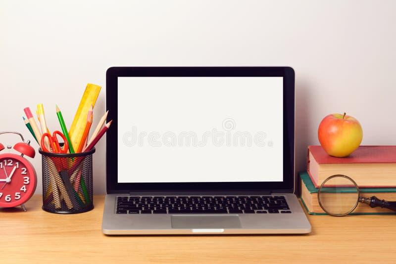 Dra tillbaka till skolabakgrund med bärbar datordatoren och böcker modern arbetsplats arkivfoton