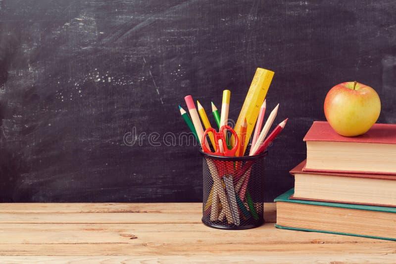 Dra tillbaka till skolabakgrund med böcker, blyertspennor och äpplet royaltyfria foton