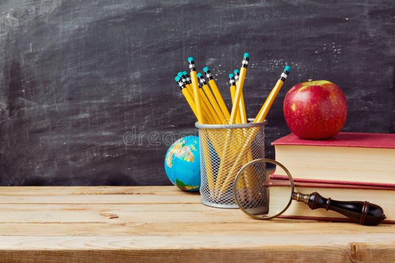 Dra tillbaka till skolabakgrund med lärareobjekt över den svart tavlan royaltyfri fotografi