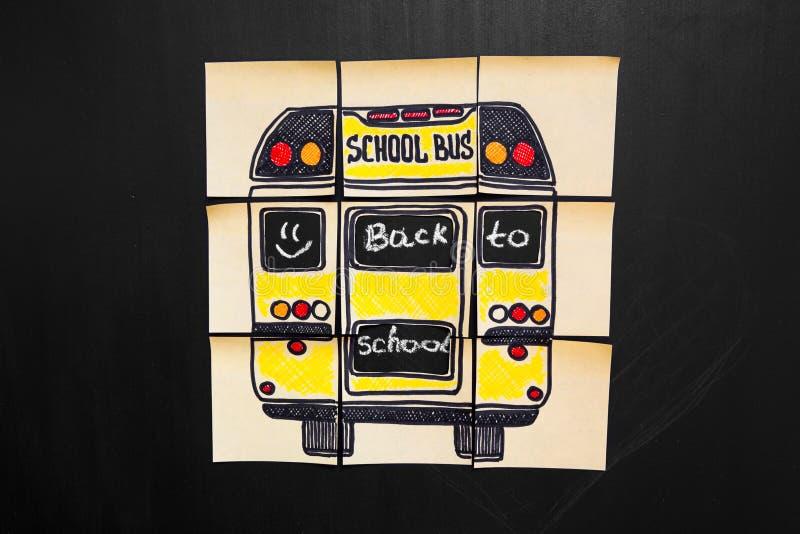 Dra tillbaka till skolabakgrund med titel` tillbaka till skola`- och `-skolbuss` som är skriftlig på de gula styckena av papper fotografering för bildbyråer