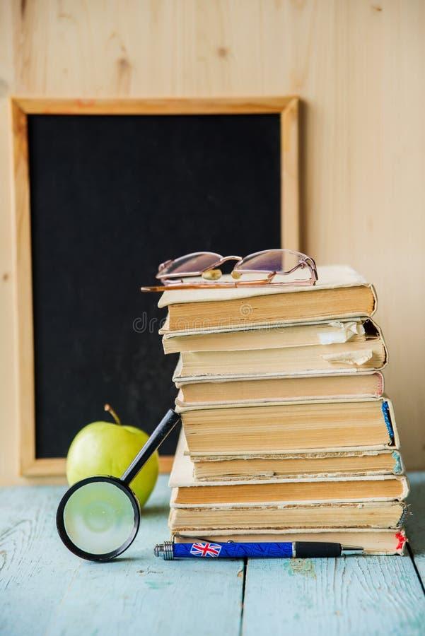 Dra tillbaka till skolabakgrund på den trätabellen och svart tavla på en bakgrund Böcker, blyertspennor, ringklocka och äpple på  royaltyfria bilder