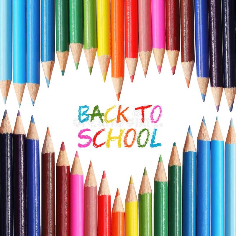 Dra tillbaka till skolabegreppet. Färgrika blyertspennor som är ordnade som hjärta. Orden 'tillbaka till den skriftliga skolan' me royaltyfri bild