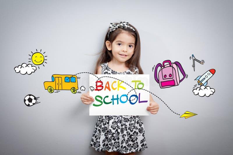 Dra tillbaka till skolabegreppet: Gladlynt le liten flickahållpapper arkivbild