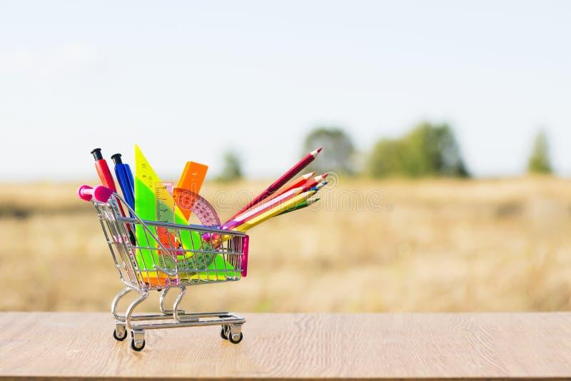Dra tillbaka till skolabegreppet med shoppingvagnen och mångfärgade blyertspennor på den vita bakgrunden Första September royaltyfri fotografi