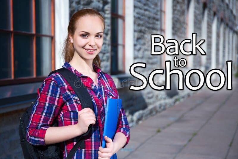 Dra tillbaka till skolan - att le den tonårs- studentflickan med ryggsäcken arkivbild