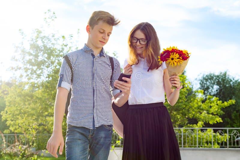 Dra tillbaka till skolan, barn som tonåringar går den första dagen till skolan, med buketten av blommor, leendet, samtal royaltyfri bild
