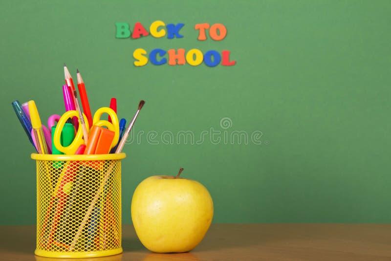Dra tillbaka till skolan. Blyertspennor, äpple och service med royaltyfria foton