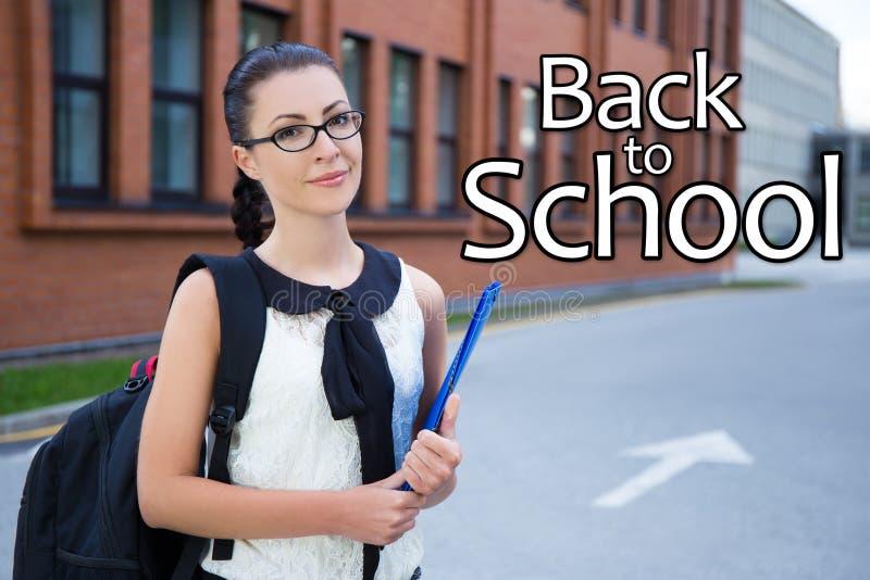 Dra tillbaka till skolan - flicka i anseende för skolalikformig i universitetsområde royaltyfria bilder