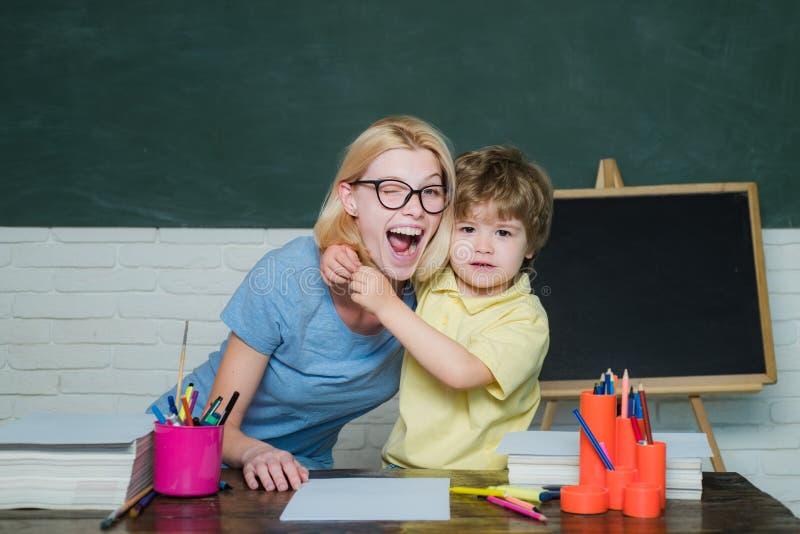 Dra tillbaka till skolan och lycklig tid L?rarinna och skolpojke i grupp p? skola H?rd examen skola f?r l?rande behandling f?r el fotografering för bildbyråer