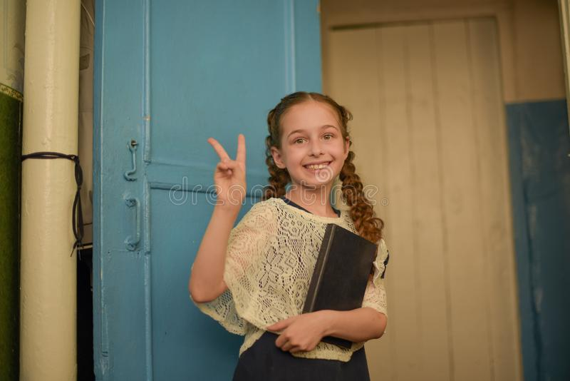 Dra tillbaka till skolan och utbildningsbegreppet Flickan rymmer den stora öppna boken Skolaflicka med den förvånade framsidan so arkivbilder